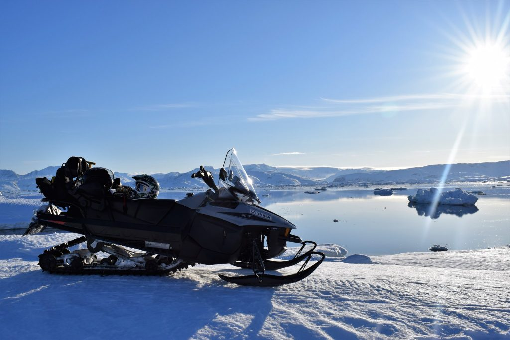 Snowmobile and view over Sermilik Fjord